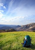 pic of cloudy  - Travel backpack standing on green grass on a background of mountains under the blue cloudy sky - JPG