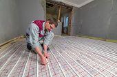 image of floor heating  - pipefitter installing system of heating - JPG