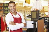picture of cashiers  - Male Cashier At Supermarket Checkout - JPG