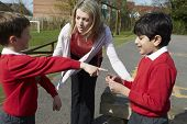 stock photo of stop fighting  - Teacher Stopping Two Boys Fighting In Playground - JPG
