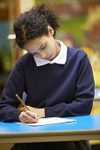 stock photo of pupils  - Female Elementary School Pupil Writing Book In Classroom - JPG