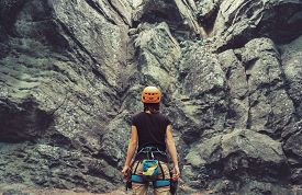 image of rocking  - Young woman wearing in climbing equipment standing in front of a stone rock outdoor and preparing to climb rear view - JPG