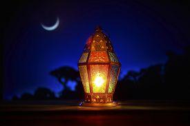 foto of ramadan mubarak card  - An illuminated colorful ramadan lantern against blue night sky with an crescent moon - JPG