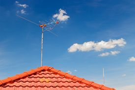 image of antenna  - old TV antenna on roof photoblue sky background - JPG
