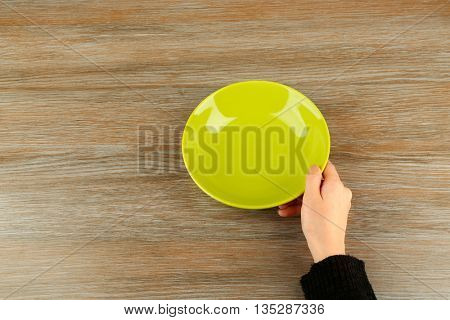 Woman hands holding empty plate, top view