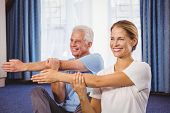 Portrait of fitness instructor and senior stretching their arms during fitness class poster