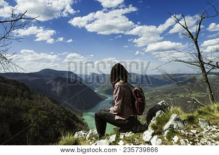 poster of Girl relaxing on a beautiful mountain view. Traveler sitting on mountain rock enjoying beautiful mountain view.  Traveler. Travel. Mountain view. Mountain peak. Outdoor traveler. Backpack traveler. Traveling alone. Hipster traveler.