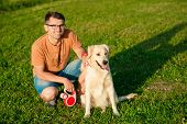Portrait Of Young Man Sitting Hugging With Golden Retriever Dog. Friendship, Pet And Human. Man Play poster
