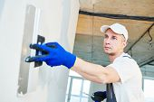 Plastering. Worker spackling a wall with putty poster