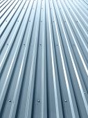 Corrugated Shiny Metal Plates On Industrial Building Roof With Rivets And Bolts poster