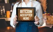 Close Up Woman Barista Holding Tablet And Show Bitcoin Accepted Here On Tablet Screen At Cafe Counte poster