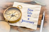 See life as a journey  - inspiraitonal handwriting on a napkin with an antique brass compass poster