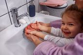 Washing Hands Is Funny- Mother And Smiling Kid Girl Wash Hands With Soap In Bathroom At Home poster