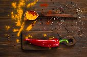 Постер, плакат: Traditional Indian Flowers Holi Spices A Large Wooden Spoon And Red Pepper On A Dark Background B