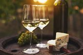 Two Glasses Of White Wine On The Old Wooden Barrel Outdoors. Sunset In The Vineyard. poster