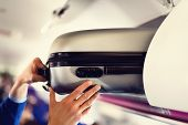 Hand-luggage Compartment With Suitcases In Airplane. Hands Take Off Hand Luggage. Passenger Put Cabi poster