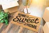 Wman in Pink Shoes and Sweats Standing Near Home Sweet Home Welcome Mat, Boxes and Plant. poster