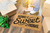 Man and Woman Standing Near Home Sweet Home Welcome Mat, Moving Boxes and Plant. poster