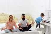 Young Parents Meditating, While Their Little Son Playing Piano, Annoying Parents. Couple Do Yoga Exe poster