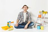 Male In Newspaper Hat With Pencil Behind Ear Sitting On Floor With Instruments For Renovation Apartm poster