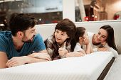 Young Happy Family Checks On Softness Of Orthopedic Mattress, Lying On Bed In Furniture Store. Young poster