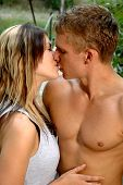 pic of beautiful brunette woman  - A loving young couple kissing near a bridge - JPG
