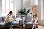 Young Strict Mother Or Sister Scolding Stubborn Sulky Kid Girl In Living Room At Home, Offended Daug poster