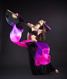image of belly-dance  - young beauty girl in arabic costume dance with fantail and purple veil in dark - JPG