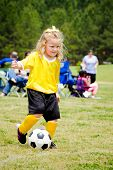 stock photo of little-league  - Cute young girl in uniform playing in organized youth league soccer game - JPG