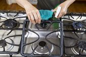stock photo of house cleaning  - Hands lifting front grill of stove top range with spray bottle in hand