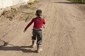 Naughty Child Running Along A Dusty Road. poster