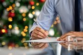 Close up of formal businessman hand signing document in office with decorated christmas tree in back poster