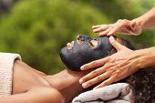 Hands of masseuse applying black charcoal mask on african woman face. Young woman getting black mask poster