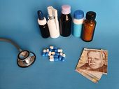 Peruvian Banknote Of Twenty Soles, Stethoscope, Medicine Bottles And Pills On The Blue Background poster