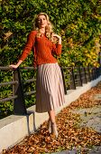 Girl Gorgeous Blonde. Femininity And Tenderness. Woman Walking In Autumn Park. Pleated Skirt Fashion poster