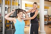 smiling teenage woman exercising in gym with trainer