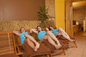 three smiling women in front of sauna posing thumbs up