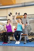 smiling young women in gym posing thumbs up