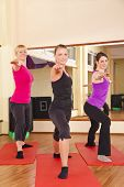 three young women performing stretching exercise