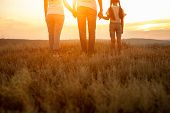 Crop Parents And Daughter Holding Hands And Admiring Sundown In Nature While Representing Love And R poster