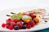 stock photo of crepes  - fresh tasty homemade crepe pancake with chocolate sauce fruits and berries - JPG