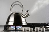 stock photo of kettling  - Tea kettle with boiling water on gas stove - JPG
