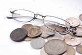 stock photo of tithe  - pic of old coins and eyeglasses on white back - JPG