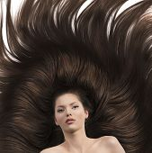 stock photo of nacked  - pretty brunette lying on her long brown hair laying down she looks in to the lens with nacked shoulders - JPG