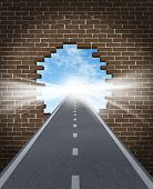 stock photo of overcoming obstacles  - Break through to opportunity concept with a highway going through a broken brick wall to a shinning light of success on a sky background as a business icon and a symbol for a new life vision - JPG