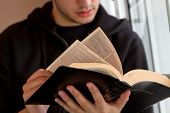 picture of bible story  - Young man reading the King James Bible - JPG