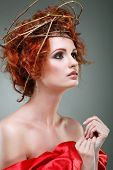 Red hairs. Portrait of beautiful girl in red fabric in a chaplet from branches.