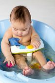 Baby boy in a bathtube bathes with toys