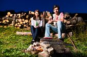 Tyrol - Young couple sitting on alpine meadow of a mountain on Campfire in the Bavarian Alps enjoyin