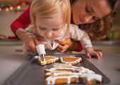 picture of christmas baby  - Baby helping mother decorate homemade christmas cookies with glaze